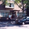 F2746<br /> Het bureau van de politie Sassenheim aan de Menneweg.<br /> De foto moet genomen zijn in het voorjaar van 1994. Aan de gevel hangt al het nieuwe politielogo en aan de mast hangt een vlag met ook het nieuwe logo.<br /> De politieman die langsloopt: John Jasperse.