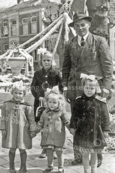 F0917 <br /> Leen van Klaveren op de Oude Haven tijdens de bloemencorso. Naast hem zijn dochter Annie. Op de voorgrond v.l.n.r.: de dochters Jannie, Lenie en Truida. Op de achtergrond de met narcissenslingers versierde fontein. Foto: ca. 1952.
