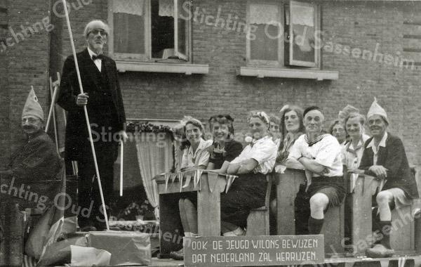 F1088 <br /> Bevrijdingsoptocht op 31-8-1945. Stelt waarschijnlijk een klas voor van de School met den Bijbel. Tweede van links (met stok) is Roel de Nobel; derde man van links Gerrit Kersten (?); tweede vrouw van links: Laura van Steensel; derde vrouw van links Cor Pit-Wijntjes; vijfde vrouw van links is Aal Plagmeijer.