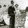 """F3022<br /> Bevrijdingsoptocht 1945.<br /> De bruid is mevr. Mien van der Zwart-de Rooy, zij """"trouwde"""" met haar buurman. Haar echtgenoot, Cor van der Zwart is de man met de fiets. Het bruidsmeisje is dochtertje Rietje van der Zwart"""