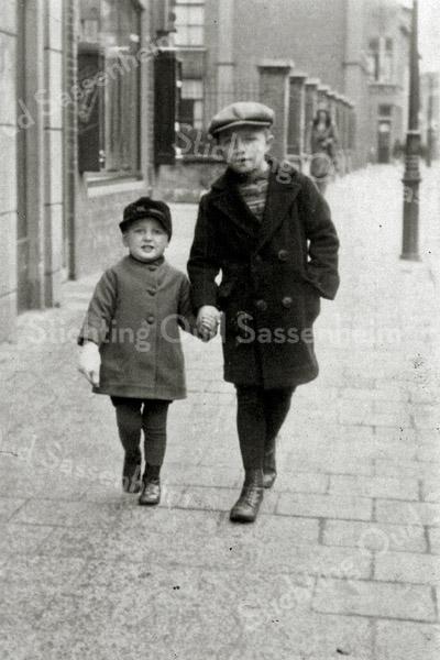 F0955 <br /> Klaas Overvliet, wandelend met zijn broertje Gijs ter hoogte van het huis van Vogelaar. Op de achtergrond het hek van het hervormde verenigingsgebouw, dat stond op de plek waar nu het dorpsplein is. Foto: ca. 1932.