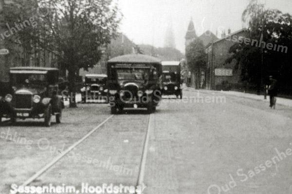 F0354 <br /> Sassenheim-noord: de Hoofdstraat ter hoogte van de Molenstraat, gezien in zuidelijke richting. Links staat een Ford geparkeerd en op de rails rijdt een lijnbus, de zogenoemde Brockway. Dat was een groene bus met op de achterzijde een ooievaar geschilderd. Later werden deze bussen vervangen door een zogeheten 'wilde dienst' met rode bussen van Sommeling. Concurrentie voor de stoomtram! Op de achtergrond het torentje van het pand van Barend van Loo en links daarvan de toren van de r.-k. kerk St. Pancratius. Foto: ca. 1930.