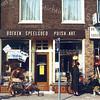 F0246 <br /> De winkel van Van Steijn, Hoofdstraat 171. Een bekend adres voor souvenirs, boeken, speelgoed en huishoudelijke en religieuze artikelen. Op de foto de aanplakbiljetten voor opheffing van de winkel. Nu is er de kledingzaak DK-studio in gevestigd. De zaak rechts, De Houtschuur, bestaat ook niet meer; daar is nu Shaffy's bar & restaurant. Geheel links is nog juist Jolentha Mode te zien, nu (2016) behorend tot de keten Bjoetie Eksklusief. Foto: 1984.