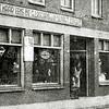F2689<br /> De winkel van Lascaris aan de Hoofdstraat 234b. In de deuropening staat mevr. Lascaris en dochter Tiny.