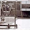 F2464<br /> Onder het donkere afdak is de ingang van sporthal Wasbeek te Sassenheim. Foto: 2000.