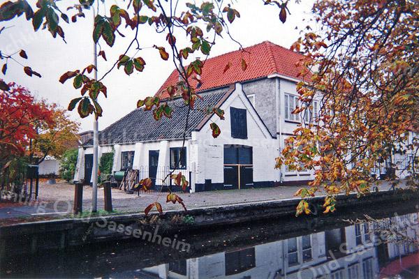 F0087 <br /> De asschuur aan de Vaartkade, waarover in de jaren negentig zoveel te doen is geweest. De schuur stamt uit de 19de eeuw en diende voor opslag van as, dat bij de bevolking werd opgehaald. De as werd via de Sassenheimervaart (die waarschijnlijk al in de 17de eeuw werd gegraven) naar Leiden vervoerd voor de fabricage van zeep. In de jaren negentig had H. Warmerdam er zijn schoenmakerij. Het pand is gesloopt in 2002. Foto: 1996.