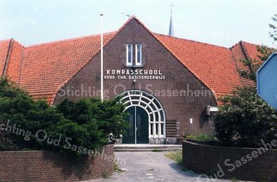 F0056 <br /> De Kompasschool voor chr. basisonderwijs, gelegen aan de Jacoba van Beierenlaan. Gebouwd in 1930 als Nederlands-hervormde school. Het gebouw op de foto valt op door het enorme dak en de zware dakgoten. Het was indertijd een mooi gebouw, maar is er door latere verbouwingen niet mooier op geworden. In 1994 gingen de Kompasschool, De Wegwijzer aan de Diligence en Het Anker aan de Kagerdreef samen tot de prot.-chr. school De Rank. De torenspits boven het dak is van de Ned.-herv. kerk. Foto: ca. 1985.