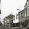 F1993<br /> De Hoofdstraat gezien in zuidelijke richting. Rechts het pand van kapper Fok van Dijk, dan de Gasspecialist, wijnhandel van Van Niekerk en 't Bruine Paard.