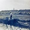 F0012 <br /> Meeuwissen sr. is bezig met een schepnet snoekvisjes te vangen om ermee te snoeken. Achtergrond: Hein Baderstraat en de toren van de r.k.-kerk St.Pancratius. Voorgrond: de Scheisloot, grens tussen Sassenheim en Voorhout. Rechts de roeiboot van Meeuwissen. Foto: ca. 1930.