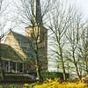F0512 <br /> Een weelderige begroeiing vóór de kerkhofmuur van de Ned.-herv. kerk (Dorpskerk) in de lente van 1999 met de kerk op de achtergrond. Foto: 1999.