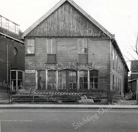 F1596 <br /> Links naast het schoolplein van de 'School met den Bijbel' lag de timmerwerkplaats van de fa. J. Dijkstra & Zn. Het complex was uit hout opgetrokken en is naderhand vervangen door een stenen gebouw. Links het woonhuis van de fam. Dijkstra.