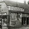 F0023 <br /> De kruidenierswinkel van Mathôt, gevestigd op Hoofdstraat 157 (oude huisnummering) met de ouderwetse reclameborden van 'Van Nelles tabak', reclame voor cacao, 'Erdal schoensmeer' en op de winkeldeur 'Rinse Appelstroop'. (Op deze plek staat nu (2016) het pand van ABN-Amro.) De transportfiets met de mand staat voor de deur en voor de kozijnen van de huiskamer hangen nog donkergroene luiken. Vóór de winkel een gaslantaarn.   Foto: ca. 1926.