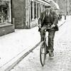 F2973<br /> Martinus Herruer op de fiets in de Hoofdstraat ter hoogte van kruidenierswinkel Van Goeverden.
