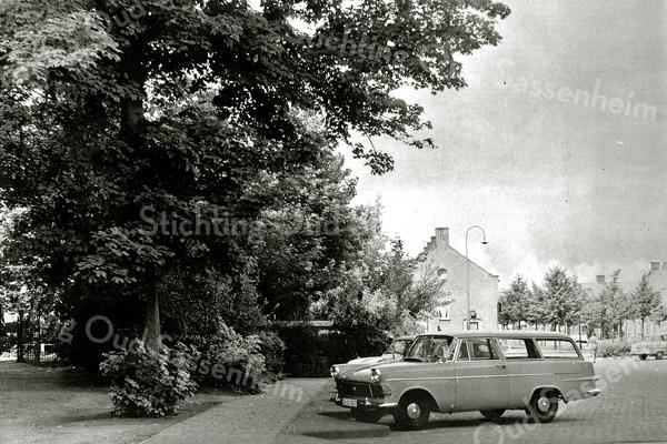 F1197a <br /> Foto F1197a en b horen bij elkaar. Foto F1197a laat de lommerrijke ingang naar de herv. kerk zien. Tussen de bomen zien we een deel van de oude kerkhofmuur. Rechts de Hortuslaan. Foto F1197b sluit aan de rechterzijde van deze foto aan. Foto: jaren '70.