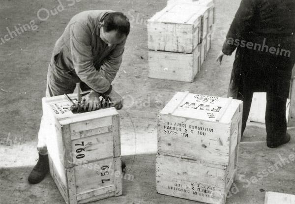F0932f <br /> Personeel van Gebr. Van Zonneveld & Philippo, bezig met het verzendklaar maken van de kisten met bollen of knollen. Met stalen banden worden de kisten hermetisch afgesloten.