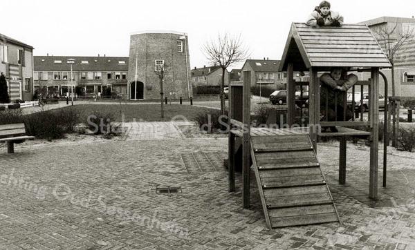 F2267<br /> De speelplek in de J.J. van Rhijnstraat. Op de achtergrond de molenstomp van de voormalige molen De Nijverheid, ook wel de 'molen van Speelman' genoemd.