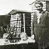 F2658<br /> Deze foto is genomen in de tuin van Zuiderstraat 37. De bollenkisten zijn van Z&P.<br /> Mevr. Heijns-Keijzer met de tweeling Kees en Wils. Foto: 1933