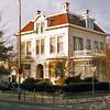 F2898<br /> Villa Anna Margaretha op Hoofdstraat 153 is een Rijksmonument. Het staat op de linkerhoek van de Hoofdstraat en de Julianalaan en werd in 1915 gebouwd  door de fa. J.E. Dijkstra voor Hans Speelman, zoon van Elias Speelman. In de na-oorlogse jaren was hier de AMRO Bank gevestigd.  Eind jaren '50 tot ca. begin jaren '80 was hier het Accountantskantoor Otto gevestigd. Daarna de fa. Leeuwenbergh BV. Foto: 1992.