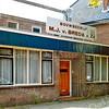 F2017<br /> Bouwbedrijf van aannemer M.J. van Breda & Zn, gezien vanaf de Hoofdstraat aan de linkerkant van de Kerklaan. In vroeger jaren was in dit pand het bollenbedrijf van de Gebr. Aangeenbrug gevestigd. Wordt binnen niet al te lange tijd gesloopt. Foto: 2009.
