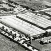 F0560 <br /> Aan de straat de koek- en banketfabriek, die toen Othello heette. Nu staat er al jaren Ravensbergen Food B.V. waar toonaangevende mueslirepen en gebakken granenrepen gemaakt worden. Het witte huis op de voorgrond, op de hoek van de Hoofdstraat, werd bewoond door N. Bruidegom. Bovenaan rechts het bollenbedrijf van P.A. le Clercq. Het pad naar dat bedrijf is nu (2016) de Jagtlustkade. Links bovenaan zien we de bedrijfsgebouwen van de Johnson Wax-fabriek, die zich hier in 1951 vestigde; in 1964 verhuisde het bedrijf naar Mijdrecht. Nu (2016) staat drukkerij Elburg-Smit op deze plaats. Linksonder zien we het bollenland van Bulbhorst. Foto: jaren '50.