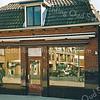 F1934<br /> De winkel van de Fruit-Faas aan de Hoofdstraat te Sassenheim. Rechts van de winkel de slagerij van Van den Berg. Nu (2016) zijn hier diverse winkels gevestigd, waaronder de Etos, met appartementen erboven. In de winkelruiten zien we de appartementen aan de Hortuslaan weerspiegeld.