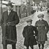 F0008 <br /> Jan Hogewoning sr. met zijn zoons Arie (rechts) en Albert (midden) op de Hoofdstraat, ter hoogte van nu (2021) bakker Jongeneel. Links de winkel van Bemelman, schilder, behanger en verkoper van klompen. Daarnaast het huis van Vos, de kolenboer. De r.k.-kerk St. Pancratius op de achtergrond. De stoomtram reed toen nog. Foto: ca. 1931.