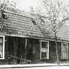 F0537 <br /> J.P. Gouverneurlaan. Een rij oude huizen uit het begin van de vorige eeuw met rechts op de hoek van de Hoofdstraat de bloemenzaak van Van Eeuwen. Later was hier de viswinkel van Nic. Roos gevestigd. Het poortje rechts van het eerste huis leidde naar het slachthuis van slagerij Couvée.  In 1964 is alles gesloopt en vervangen door winkels met daarboven gelegen appartementen. Foto: jaren '60.