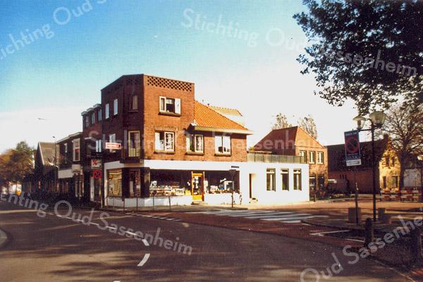 F0186 <br /> Hoek Hoofdstraat/Kastanjelaan met de bekende drogisterij van het echtpaar Melman-v.d.Nouland. De drogisterij is verdwenen. Uiteindelijk is het pand in 1997 bij de Digros getrokken (in 2016 Dirk). De panden rechts daarvan zijn nu nog zoals ze op de foto staan, maar de panden links, zoals van kapsalon Heemskerk zijn opgekocht en ook bij de Digros getrokken. Op deze foto is goed te zien tot hoe ver de overkluizing van 1966 loopt, nl. tot het roodwitte hek.   Foto: 1971.