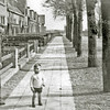 F2926<br /> Het tweede gedeelte van de Kerklaan richting Lindenlaan. Op de voorgrond Dhr. Jaap Baardse met zijn zoon. Het achterste gedeelte van de Lindenlaan moet nog worden gebouwd.  Foto: ca 1930