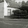 F0517a <br /> Het huis van de voormalige grossier in grutterswaren A.W. Tijssen. Het is een van de oudste huizen van Sassenheim, een langgerekt wit huis aan de Hoofdstraat, afgebroken in 1964. Nu (2016) zijn hier Apotheek Sassenheim en hengelsportzaak AHOY gevestigd.  Vóór de fam. Tijssen woonde hier deurwaarder Van Dorp. Links van het witte huis was de ingang naar de St. Pancratiusschool. Foto: 1962.