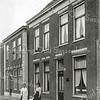 F0807 <br /> De beide dames met kind staan voor het in 1892 gebouwde huis van de weduwe D. Rijnsburger aan de oostzijde van de Hoofdstraat. In dit pand kwam later de winkel van Jamin; anno 2016 is Blue-In erin gevestigd, nu Hoofdstraat 268. Het pand links ervan werd eveneens in 1892  gebouwd  voor W. Rijnsburger Dzn. Foto: vóór 1921. ('Rijnsburger' was de toenmalige schrijfwijze, getuige ook de Kieslijst van 1918. Later is de -h- ertussen gekomen.)<br /> <br /> Collectie Oudshoorn 004: huis wed. D. Rijnsburger 1892, Hoofdstraat 200 volgens oude nummering.<br /> .