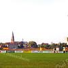 F0127 <br /> Gezicht op Sassenheim gezien vanuit het oosten. Het terrein van de rugbyclub The Bassets op de voorgrond. Daarachter het ontruimde terrein van de voetbalverenigingen Ter Leede en Teylingen. Hier is de nieuwe woonwijk Mennepark gebouwd. Rechts de woonflat Parkhove. Op de achtergrond het gymnastieklokaal, de huizen aan de Parklaan en de r.-k. kerk St. Pancratius.   Foto: 1997.