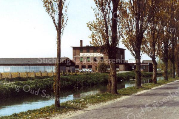 F0272 <br /> De bollenschuur van de Gebr. Doornbosch & Co N.V. aan het toenmalige einde van de Postwijkkade. Dit bedrijf heeft plaats moeten maken voor huizenbouw in de Postwijk in 1984. Ook de hoge populieren aan de Zandslootkade zijn verdwenen en vervangen door andere bomen.  Foto: eind jaren '70.
