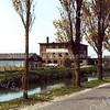 F0272 <br /> De bollenschuur van de Gebr. Doornbosch & Co. aan het toenmalige einde van de Postwijkkade. Dit bedrijf heeft plaats moeten maken voor huizenbouw in de Postwijk in 1984. Ook de hoge populieren aan de Zandslootkade zijn verdwenen en vervangen door andere bomen.  Foto: eind jaren '70.