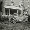 F0894 <br /> De Grof- Hoef- en Kachelsmederij met winkel van Ph. Bakker in 1912/13 aan de Hoofdstraat. Flip Bakker (uiterst rechts) staat met zijn personeel trots bij zijn eerste zelf gebouwde auto. Uit de ramen kijken zijn vrouw en dochter Coba toe. Het pand stond op de plaats waar nu Duynstee is gevestigd. Foto 1912/13.