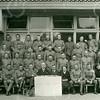 F4231<br /> Mobilisatie. Een groep soldaten voor het gebouw van de Herv. School (Kompasschool). In het midden achter het bord zit dhr. A.D. den Haan; ds. W.G. Krijkamp; dhr. Varkenvisser (concierge op de Hervormde School) en mevr. Varkenvisser. Foto: 1939