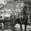 F1064 <br /> De foto is genomen voor Hoofdstraat 294, het adres van aannemer Dijkstra. Op het paard zit Jaap Dijkstra (1925), daarachter staat J. Nicola. De wagen is geladen met kisthout. Foto: 1931.