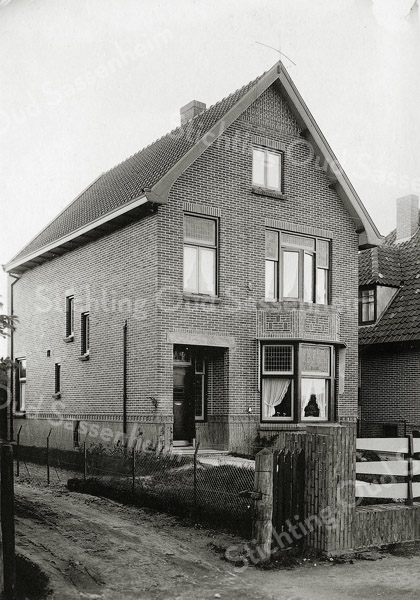 F0869 <br /> Huis aan Hoofdstraat 351, voorbij het kruispunt Sassenheim-noord. Het pad links ervan is de toegang naar de erachter gelegen bollentuin De Krocht (fa. L. van Leeuwen & Zn, later o.m. ook W. Kruik, Roosa & Wilbrink, H. Roosa, C.Wilbrink & Zn).<br /> <br /> Collectie Oudshoorn 105: Hoofdstraat 351. Foto: vóór 1921.<br /> 1.