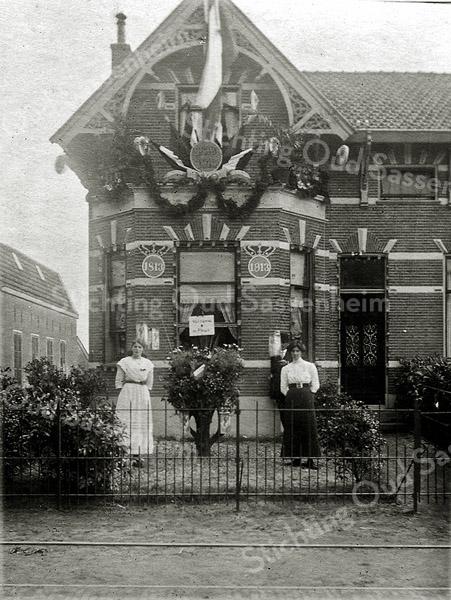 F1135 <br /> Een versierde woning aan de Hoofdstraat tegenover café-restaurant de Oude Post. Links zien we de boillenschuur van Van Zonneveld & Philippo (Z&P). Op de voorgevel ter weerszijden van het raam zien we de jaartallen 1813 en 1913. Nu staan hier de huizen van de Koningstraat.  Deze foto is genomen bij de Onafhankelijkheidsfeesten op 17 en 18 september 1913 (zie ook foto G0110). Later woonde A. Warnaar in dit pand. (Zijn bijnaam was 'Bram Politiek'.)