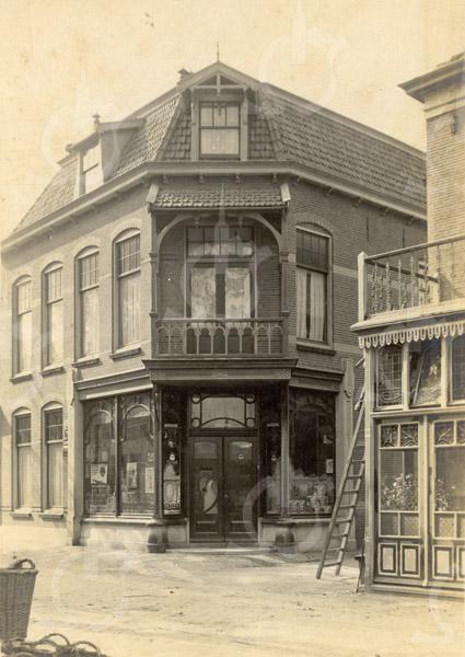 F0800<br /> Op de hoek van de Hoofdstraat en de vroegere Hortuslaan stond dit in 1906 voor A. Francken in jugendstil gebouwde grote pand. Hij vestigde zich daar als kruidenier. Later ging hij over op wijnen en sigaren. Omstreeks 1949 werd in het pand een winkel gevestigd van P. de Gruyter N.V. De gemeente kocht in 1969 het pand en liet het in 1970 slopen voor nieuwbouw van ons dorpscentrum. Rechts ziet u nog een stukje van café-hotel-restaurant 't Bruine Paard. Foto: vóór 1921.<br /> <br /> [Collectie Oudshoorn 043: winkelopstand Tabak- en Sigarenmagazijn A. Francken 1906.]