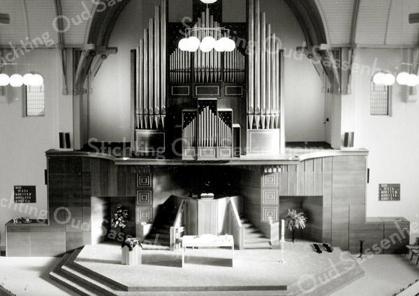 F2811<br /> Het interieur van de gereformeerde kerk in de Julianalaan na de restauratie van 1992. Het orgel is niet veranderd, maar het podium wel. De vaste opstelling van de doopvont is weg, evenals de banken ter weerszijden van de preekstoel. De hangende bollampen zijn overigens inmiddels ook verdwenen.