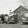 F0393 <br /> Het taxibedrijf van vader Martinus van Zoen (links) aan de Rijksstraatweg; zoon Maarten in het midden en zoon Huib rechts met hun Ford V8. Vader Van Zoen kon zelf niet autorijden, maar er stond altijd één wagen als reserve. De koffietent (eveneens eigendom van Van Zoen sr.) werd indertijd op houten rollen naar achteren gereden om plaats te maken voor een nieuwe koffietent (De Uiver). Zie ook F0136. Foto: 1938.
