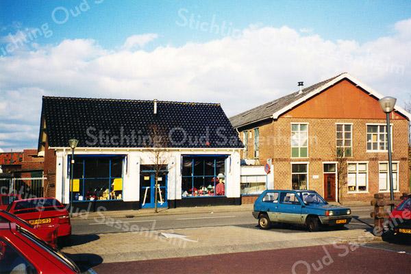 F0153 <br /> De Kunstaardewerkfabriek Velsen N.V. aan de Kerklaan, met links de showroom en rechts de fabriek. In de jaren dertig was hier het bollenbedrijf van J. Pereboom gevestigd. In 1943, gedurende de Tweede Wereldoorlog, moest de fabriek van de Duitsers vertrekken uit Velsen en werd toen gevestigd in Sassenheim (Kerklaan) onder de naam 'Velsen', waar aanvankelijk nog gebruik gemaakt werd van de oude gietmallen, maar spoedig sloegen ze daar een heel andere weg in. Vanaf dat moment produceerden ze ook Delfts Groen en Delfts Rood, beide met gouden accenten. Vaak werden kleinere zaken (zoals molentjes of asbakken) aangevuld met een deel metaalwerk. Hiervoor werd eerst het object gemaakt in de fabriek en dan doorgestuurd aan Elesva voor de aanvulling met de metalen delen. In 1953 werd de fabriek getroffen door een grote brand, die de schilderszaal en een deel van de fabriek vernielde. Om te zorgen dat het proces en verkoop doorgang konden vinden, werd de schilderszaal gesitueerd in een lokaal café (Café Juffermans aan de Warmonderdam). De chef werd geplaatst aan de bar zelf. De fabriek werd gedeeltelijk herbouwd en de zaken kwamen weer op gang. Op een bepaald moment  werd een kroontje boven het logo aangebracht, maar korte tijd later kwam men hierop terug. Alles wat nog aanwezig was met het kroontje werd vernietigd. In de jaren '80 werd gestopt met het handmatig aanbrengen van het logo en werd deze er op gestempeld. Na de verwoestende brand in 1993 werd er een doorstart gemaakt met de fabriek. Op dat moment was de fabriek in handen van de heer Steketee en had 35 medewerkers. Toen Wim van Baarle de fabriek overnam in 1995 werd er nog weinig handgeschilderd en werd een hoop vervaardigd in opdracht van andere bedrijven. Het nieuwe Velsen had in 1997 nog maar drie medewerkers, maar voor het eind van 1998 was dat verdriedubbeld en kwam Wim Neuteboom over van de Porceleyne Fles. Helaas liep de verkoop van het Delfts Blauw terug en werd de fabriek gesloten in 2002. Het pa
