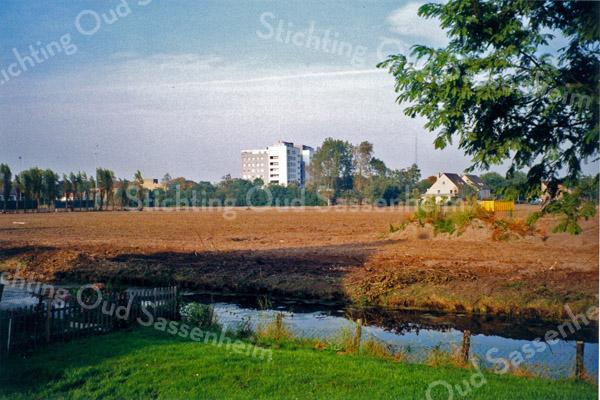 F0128 <br /> Het terrein van de voormalige sportvelden (zie F0127), waar de nieuwe woonwijk Mennepark is gebouwd. Op de achtergrond de woonflat Parkhove en de twee nieuwe huizen, waar vroeger de boerderij van Kees Breedijk stond. De foto is genomen vanaf de Grebbehove. Foto:  1997.