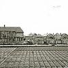 F1907 <br /> Gezicht op de Menneweg met bollenveld op de voorgrond. Het gebouw aan de linkerkant is de achterzijde van de De Visserschool, tegenwoordig Sociaal-Cultureel Centrum 't Onderdak. Foto: begin jaren '30.