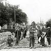 F0228 <br /> Stratenmaken bij de Oude Post. V.l.n.r.: de eerste man (geknield) is Verbeek (?); de man met meetlat is Gerrit Hogervorst uit de Zuiderstraat (?); de man met fiets is Arie van Kesteren, kantonnier in Lisse en broer van Jacobus van Kesteren; dan Roel van Dijk, die jarenlang in de Berkenlaan heeft gewoond; vervolgens de man met uniformpet; dat is Jacobus van Kesteren, kantonnier in Sassenheim; de knielende man is Cor v.d. Poel uit de Zuiderstraat, bijgenaamd 'de witte keizer'; de laatste man is onbekend. Foto: ca. 1920.