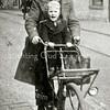 F2318<br /> Theo Landwer Johan met zoon Cees op de fiets op de Hoofdstraat ter hoogte van (toen) bakker Van der Horst. Foto: 1943.