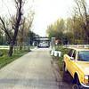 F0255 <br /> De Menneweg ten oosten van het viaduct van rijksweg A44; we kijken in westelijke richting. Op de voorgrond de Volvo van de heer Beijk, daarachter enige melkbussen van boer Theo van der Plas. De Schiphollijn is nog niet aangelegd; dat gebeurde tussen 1974 en 1982 aan de oostzijde van de rijksweg. Op de foto is het grote hek te zien, waarmee de Menneweg in oostelijke richting kon worden afgesloten. Dit was hek was geplaatst om illegaal storten van vuil op de voormalige vuilnisbelt tegen te gaan. In de praktijk kwam hier weinig van terecht, want het hek is, voor zover bekend, nauwelijks gesloten geweest. Foto: begin jaren '70.