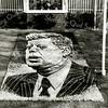 F2310<br /> Bloemenmozaïek met de afbeelding van president John F. Kennedy voor het huis van de fam. Cor Jonkman, huize Silentium op Hoofdstraat 50. Zijn zoon Jan was de ontwerper van verschillende mozaïeken, zoals Martin Luther King, zie F2310b. De naam 'Silentium' is afkomstig van een witte gladiool. Jonkman was makelaar in gladiolenkralen (zaaigoed).