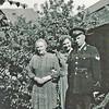 """F3829<br /> Mevr. Dingena Benschop-Verhoeven begin 50er jaren in haar tuin, op Charbonlaan 18 bij de waterput, met naast haar dochter Corrie en Piet Dieleman. Piet Dieleman was er als politieagent ingekwartierd. Omdat er toen in die huizen alleen een tappunt voor koud water in de keuken was, bracht dochter Corrie elke morgen een kom met warm water naar boven, en riep dan voor de deur van Piet Dieleman: """"Meneer, het scheerwater staat voor uw deur"""" En daar moest wel romantiek uit voortkomen en inderdaad zij zijn met elkaar getrouwd en hebben jaren aan de Rusthofflaan gewoond."""